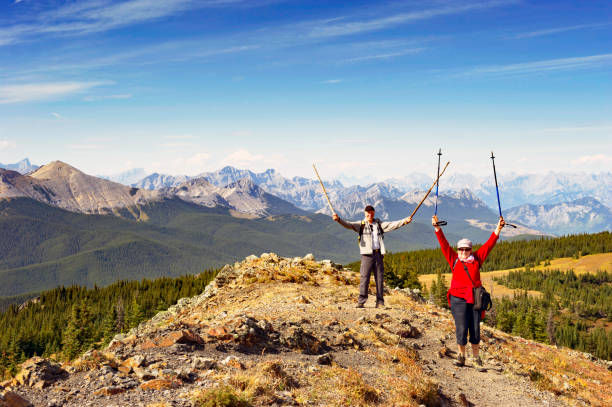 Open Arms:Cheerful caucasian senior couple with raised arms and holding walking sticks,standing  on top of a mountain during a hike in  Kananaskis Country,Alberta,Canada Senior couple reaching the top of the mountain after a hike in Kananaskis Country in the province of Alberta  during the summer months. kananaskis country stock pictures, royalty-free photos & images
