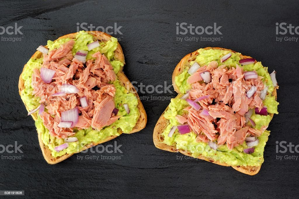 Open avocado sandwiches with tuna against dark slate​​​ foto
