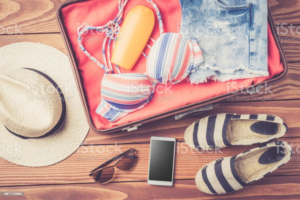 Open bag with beach accessories and clothes stock photo