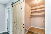 Open barn door opens to a small empty laundry room.