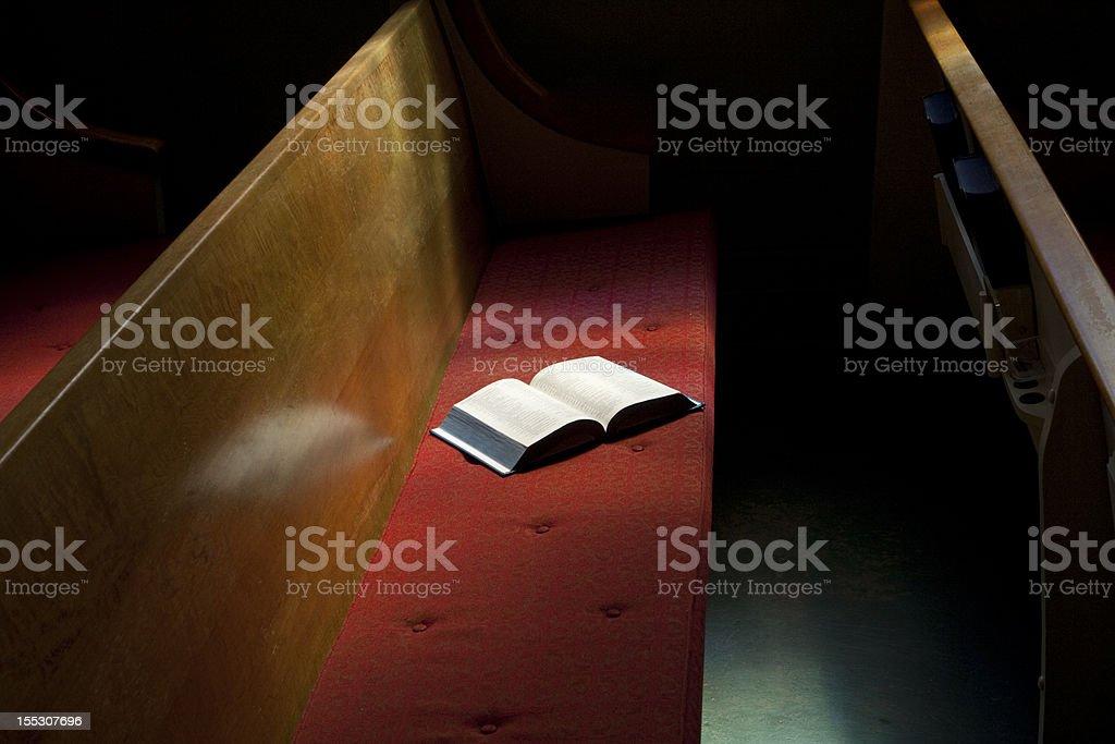 Open Bible Lying on Church Pew in Narrow Sunlight Band stock photo
