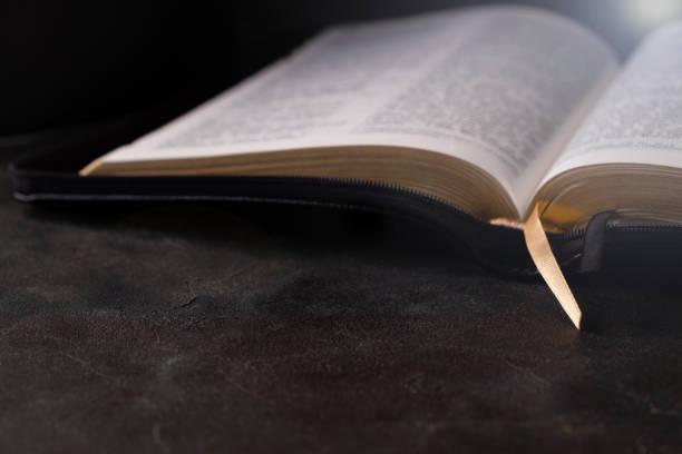biblia abierta sobre una mesa oscura con luz que viene desde arriba. concepto de cristianismo. fondo bíblico sagrado. - lifestyle color background fotografías e imágenes de stock