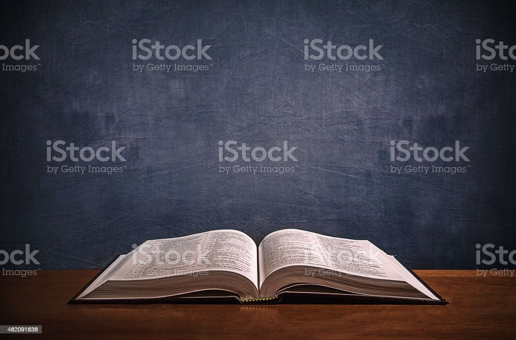 Open Bible on a wood desk stock photo