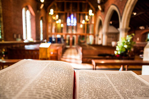 Open Bible on Altar inside Anglican Church Bible open at the book of John inside an Anglican Church of England church. The focus is on the foreground of the bible, while in the background, defocused, are the pews and arches of the historic eighteenth century building. Horizontal colour image with copy space. clergy stock pictures, royalty-free photos & images