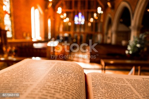 Bible open at the book of John on an altar inside an Anglican Church of England church. The focus is on the foreground of the bible, while in the background, defocused, are the wooden pews and stone arches of the historic eighteenth century building. Horizontal colour image with copy space.