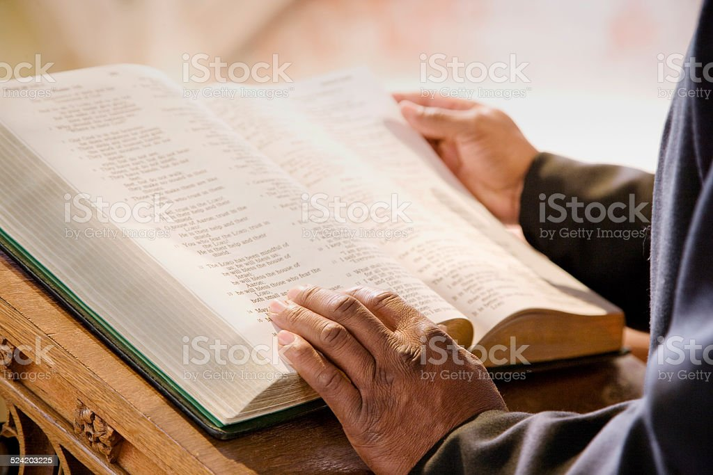 Open Bible on Church Altar With Preacher's Hands stock photo
