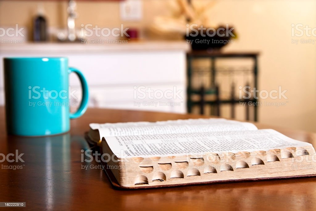 Open Bible on kitchen table with coffee mug stock photo