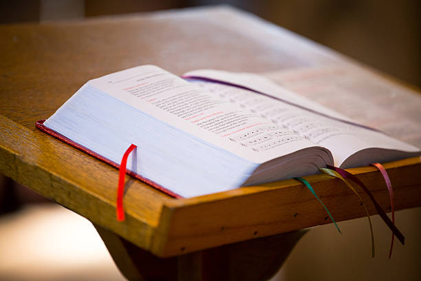 Open bible on table with bookmarks in pages Bible on the church pulpit. pulpit stock pictures, royalty-free photos & images