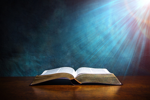 Open Bible on a wood table with light coming from above. ( church concept ).