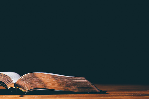 Open bible on balck background