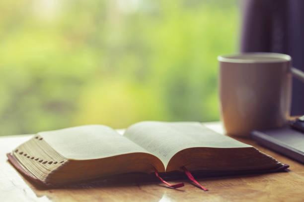abra a bíblia com uma chávena de café para a devoção da manhã na tabela de madeira com luz do indicador - cristianismo - fotografias e filmes do acervo
