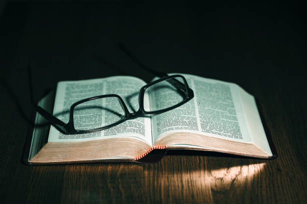 Open Bible with glasses on top stock photo