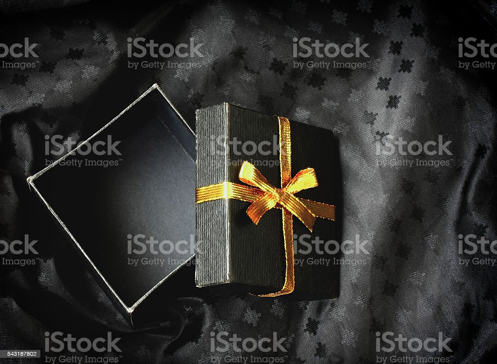open black gift box with golden ribbon stock photo