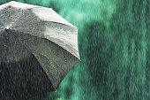 istock Open black umbrella in wet weather. Autumn rain. Deep sorrow. Wet umbrella against backdrop of street. Sad mood. Raining in city. Heavy rain on summer green background. Feel sorrow and sadness 1053791954