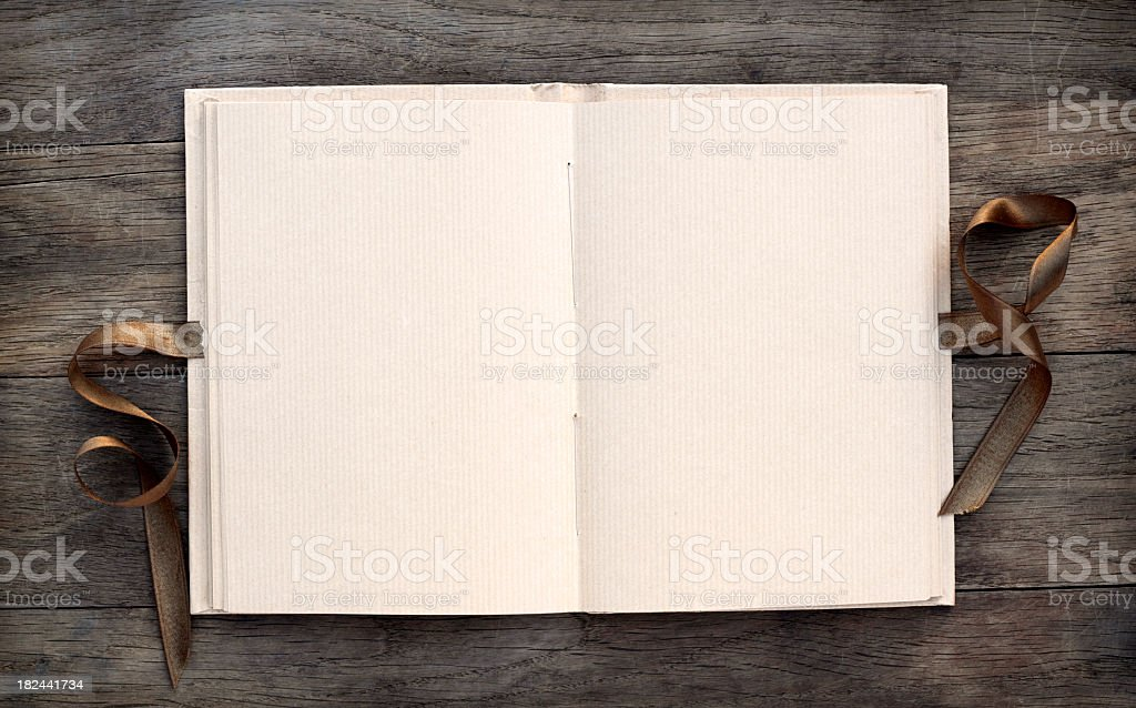 Open blank book on dark wooden table with a brown ribbon stock photo