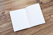 Open blank brochure, magazine is on a wooden desk