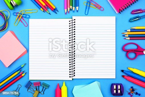 istock Open, blank lined notebook with school supplies frame over a blue background 989478784