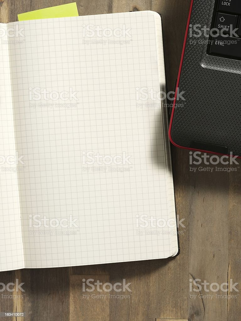Open blank notebook on the laptop royalty-free stock photo