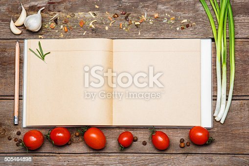 Open blank recipe book on brown wooden background with tomatoes, garlic,  green onion