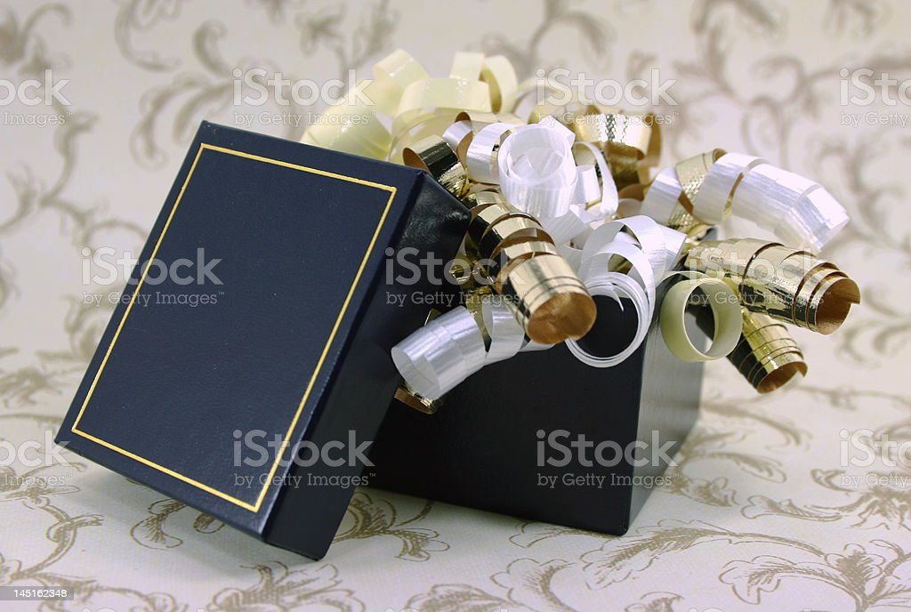 Open Blue and Gold Gift Box with Curly Ribbons stock photo