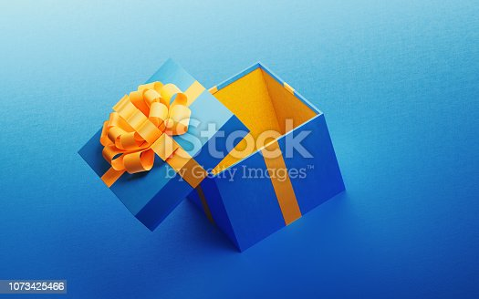 Open blue gift box tied with yellow ribbon on blue background. Horizontal composition with copy space.  Great use for Christmas and Valentine's Day related gift concepts.