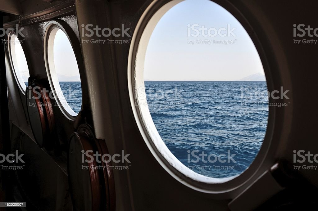 Open boat porthole with ocean view close up stock photo
