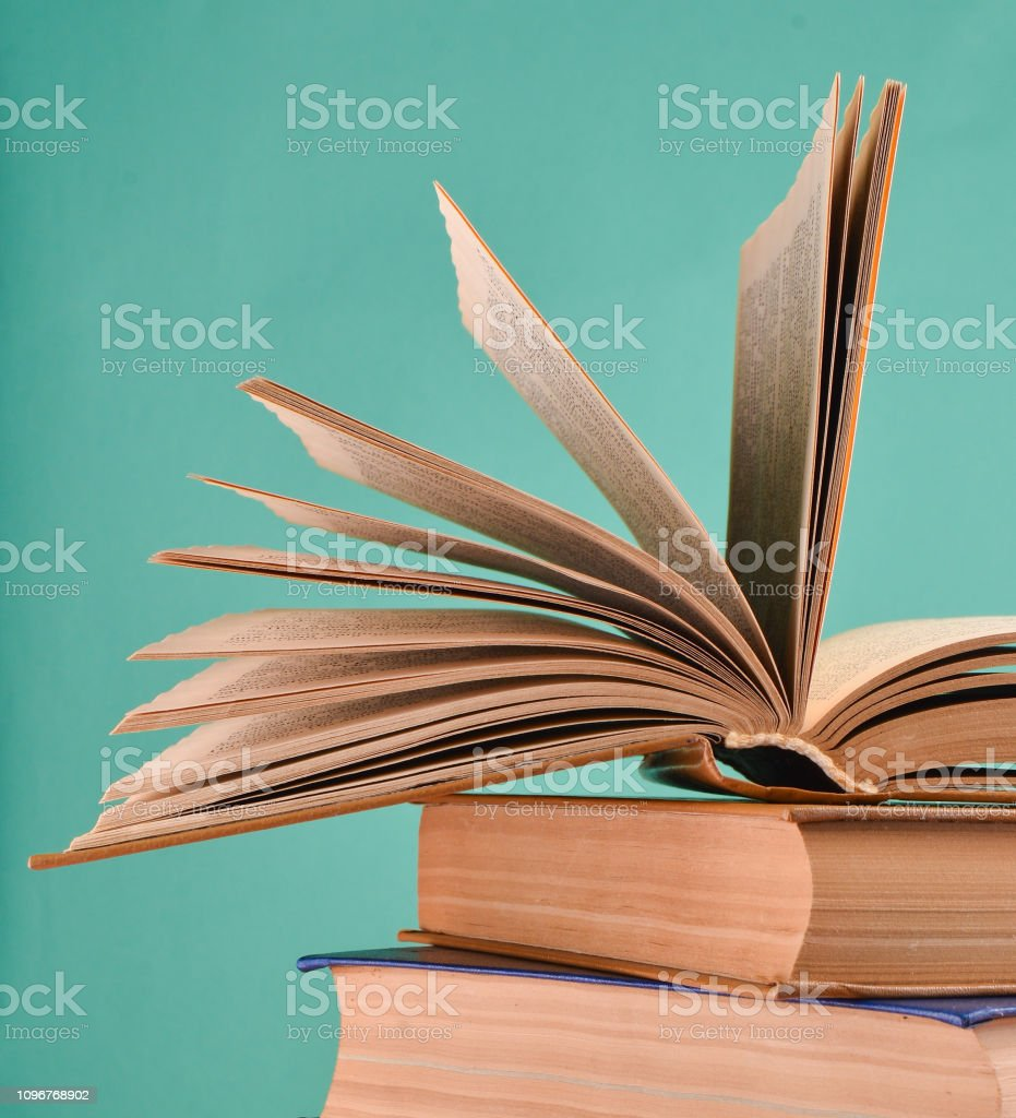 Offenes Buch, einen Stapel Bücher auf einem blauen Hintergrund isoliert. Textfreiraum, Pastell Farbe trend – Foto
