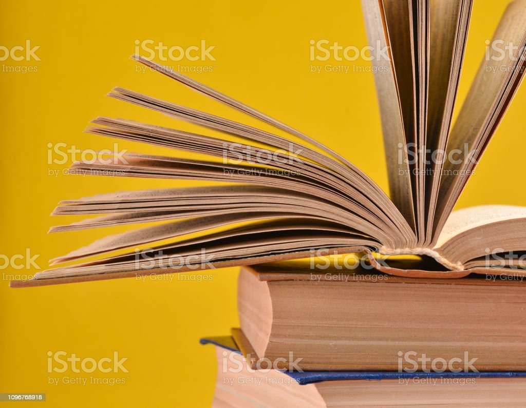 Offenes Buch, einen Stapel Bücher auf einem gelben Hintergrund isoliert. Textfreiraum, Pastell Farbe trend – Foto
