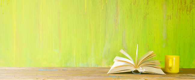 open book and a cup of coffee on green grungy background,reading, education, literature,learning, mock up, panorama with good copy space