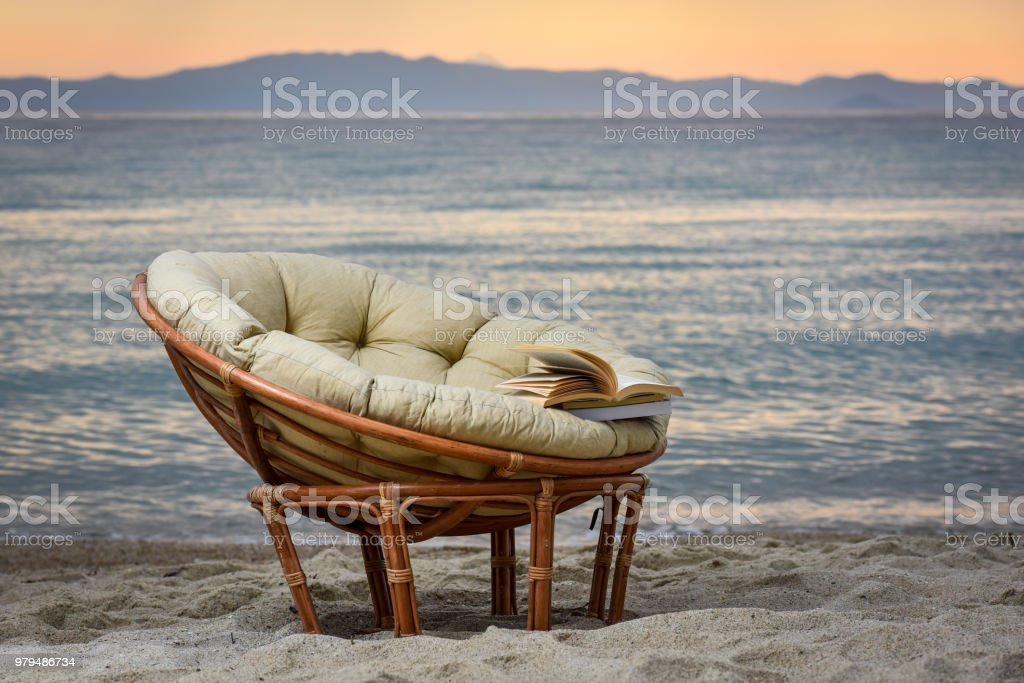 Open book and an empty chair on the beach by the sea during summer stock photo