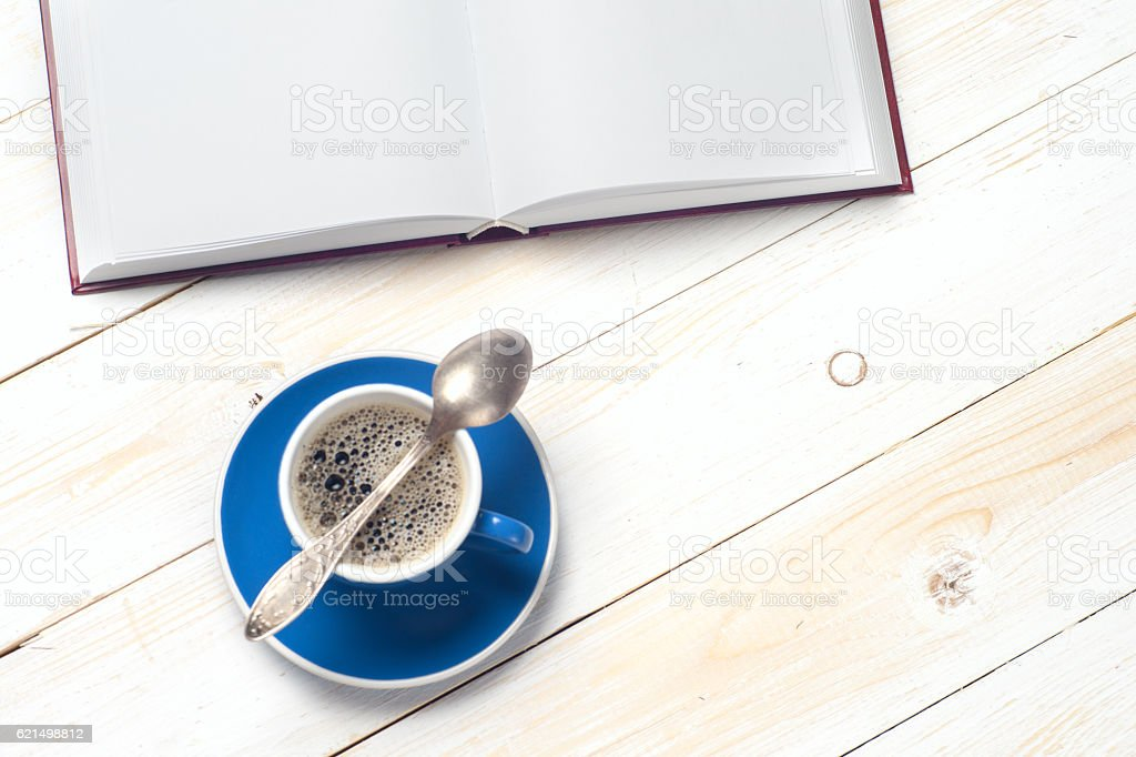Open book and cup of coffee on wooden table. Lizenzfreies stock-foto