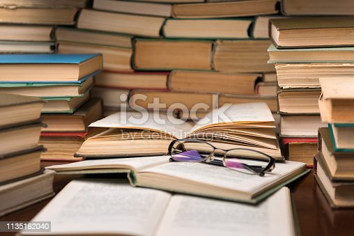 Open book and glasses on wood desk in the library room with blurred focus for education background and back to school concept