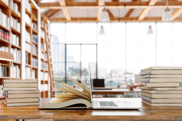 Open Book And Laptop In Library stock photo