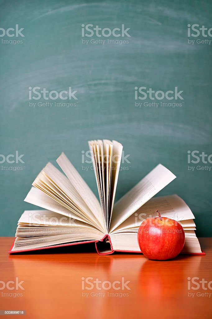 Open Book And Red Apple On A Green Chalkboard Background Royalty Free Stock Photo