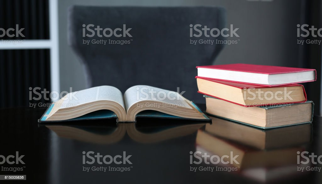 Open book and stack of hardcover books on wooden table. stock photo