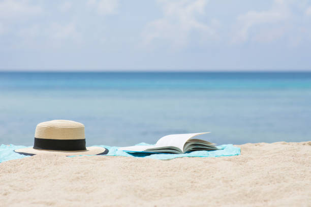 Open book and Summer hat on sarong at beach. stock photo