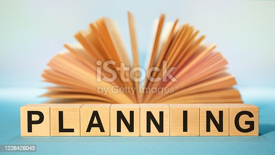 883154106 istock photo Open book and Wooden cubes with the abbreviation PLANNING 1226426043