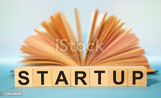 883154106 istock photo Open book and Wooden cubes with the abbreviation STARTUP 1226426049