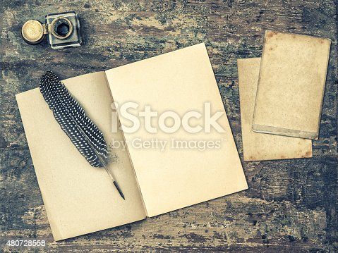 istock Open book, antique writing tools feather pen and inkwell. 480728558
