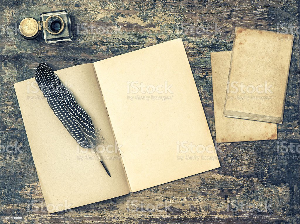 Open book, antique writing tools feather pen and inkwell. stock photo