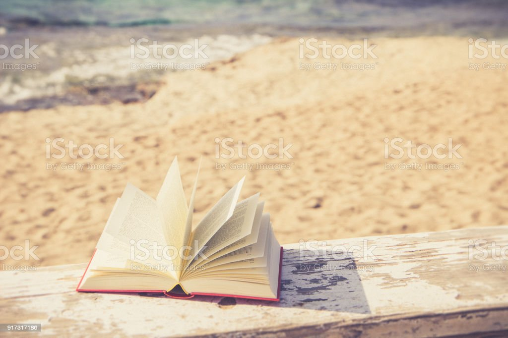 open book at the beach stock photo