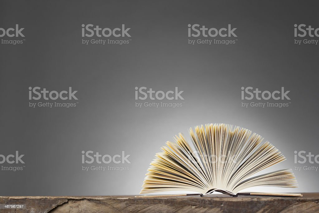 Open Book forming a fan on wooden Table stock photo