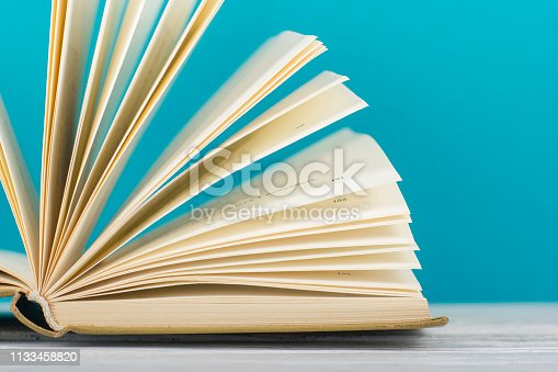 1018285596 istock photo Open book, hardback books on wooden table. Back to school. Copy space. 1133458820