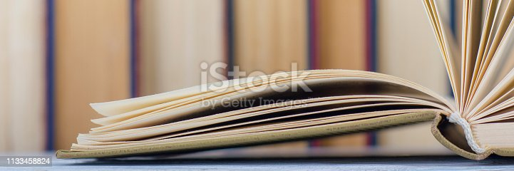 istock Open book, hardback books on wooden table. Back to school. Copy space. 1133458824