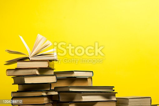 1018285596 istock photo Open book, hardback books on wooden table. Back to school. Copy space. 1204289712