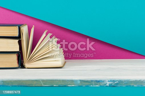 1018285596 istock photo Open book, hardback books on wooden table. Back to school. Copy space. 1206937473