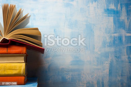 istock Open book, hardback books on wooden table. Back to school 515801588