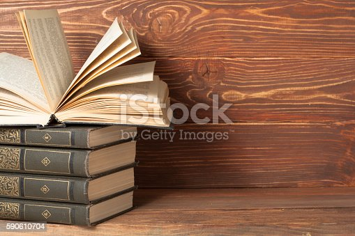 istock Open book, hardback books on wooden table. Education background. Back 590610704