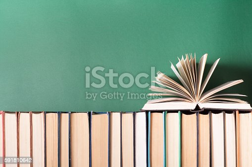 istock Open book, hardback books on wooden table. Education background. Back 591810642