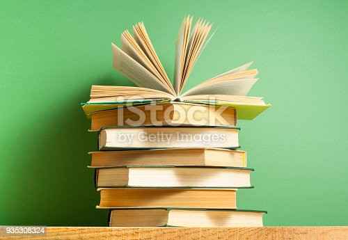 1018285596 istock photo Open book, hardback books on wooden table. Education background. Back to school. Copy space for text. 935308324